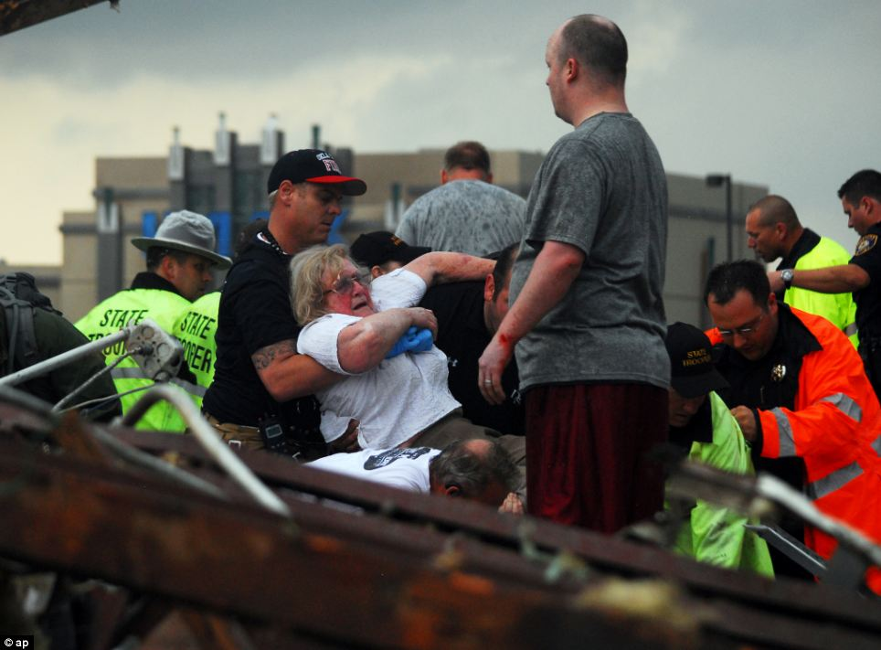 Saved: A woman is pulled from debris on Monday after the tornado barreled through