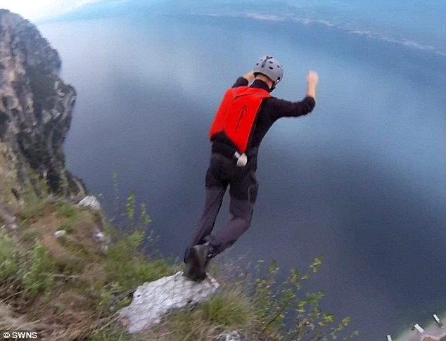 Leap of faith: Matthew, looking 1,000ft down, jumps over the edge of the cliff with the parachute strapped to his back