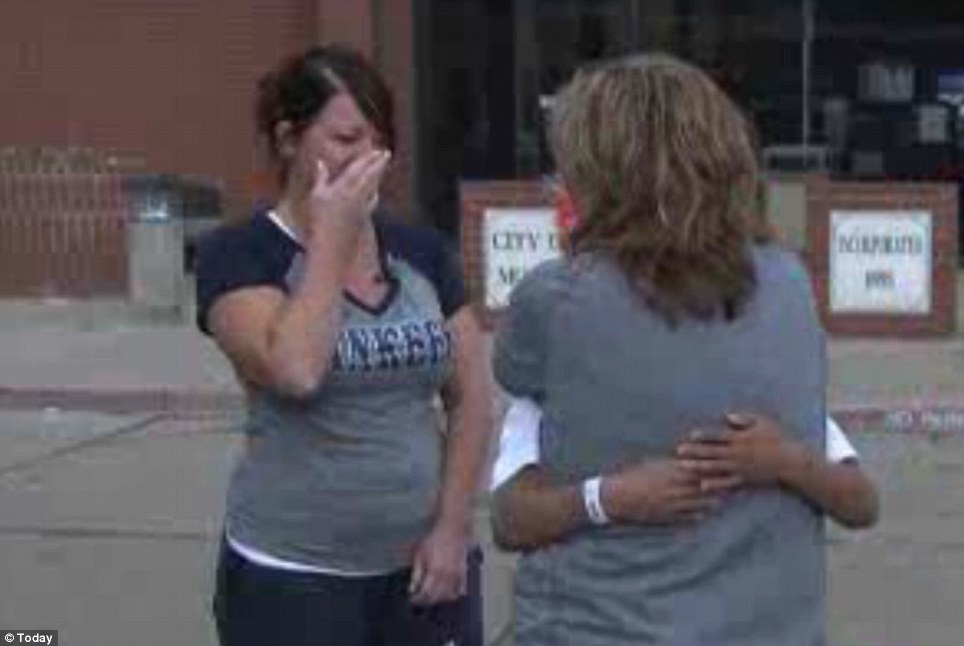 Reunited: Teacher Rhonda Crosswhite hugs student Damien Kline tightly after the young boy said his teacher saved his life as they sheltered from the tornado at Plaza Towers elementary school in Moore, Oklahoma on Monday