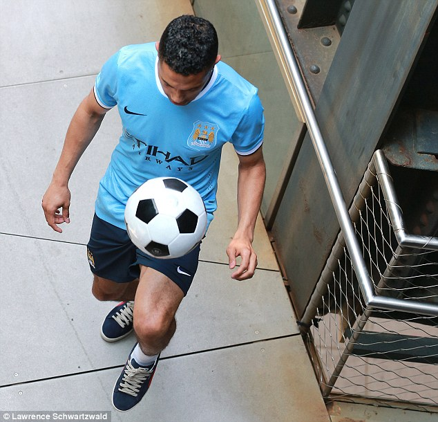 Getting involved: Gael Clichy tries the sky-blue strip out for size