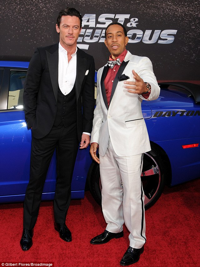 Dapper men: Luke Evans and Ludacris looked smart in suits as they posed next to a car at the premiere