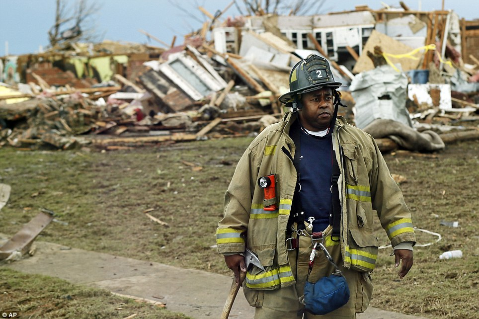 Search: A firefighter watches vehicles pass by in front of a destroyed home north of SW 149th between Western and Santa Fe on Tuesday, May 21, 2013, after a tornado struck south Oklahoma City and Moore, Oklahoma