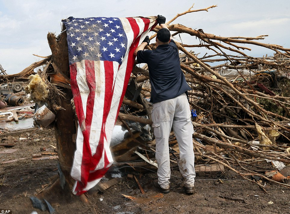 Flag: A man who asked not to be identified hangs an American flag on what is left of a tree in a neighborhood north of SW 149th between Western and Santa Fe on Tuesday, May 21, 2013