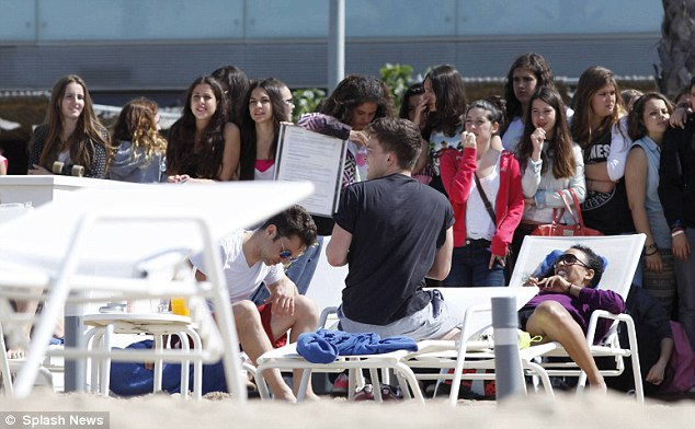 Dedicated: Groups of fans did their best to catch a glimpse of the musicians as they kicked back