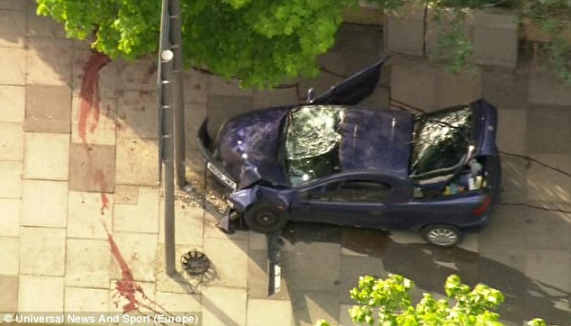 Smashed: The car used to knock the man over. A trail of blood shows where his body was dragged