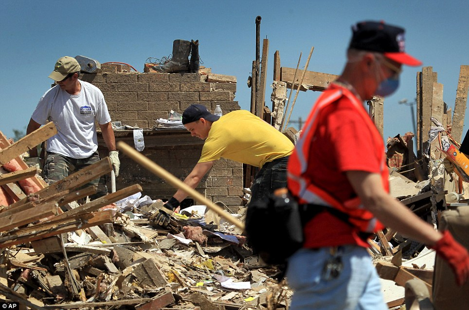 Beginning to rebuild: The happy news comes as residents and volunteers sifted through their damaged homes in Moore, Oklahoma, on Wednesday