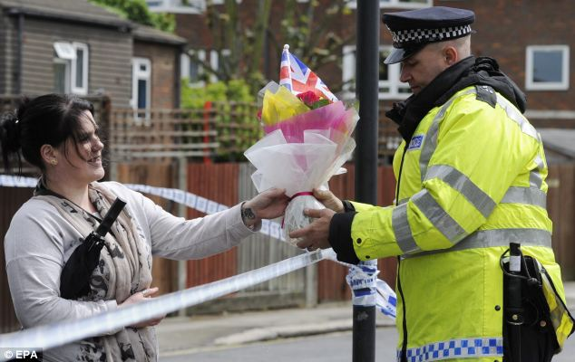 Tributes: A woman asks a policeman to lay flowers at the scene of the killing after the Ministry of Defence confirmed the victim was a serving soldier