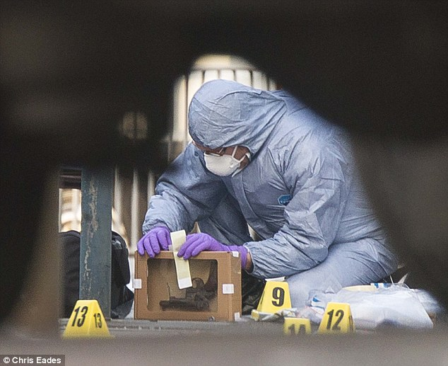 Delicate: A forensic officers examine a revolver at the scene and p0laces it in a protective box pistol close to Woolwich Barracks