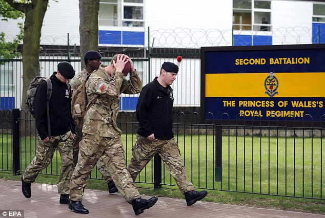 Upsetting: Soldiers leave their barracks in uniform today as they digest what has happened to a comrade