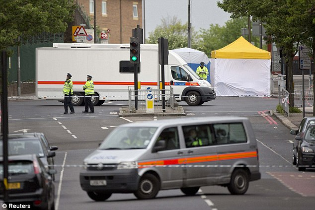 Crime scene: Scotland Yard officers guard the busy area of Woolwich where the attack happened, which Prime Minister David Cameron confirmed was a likely terror attack