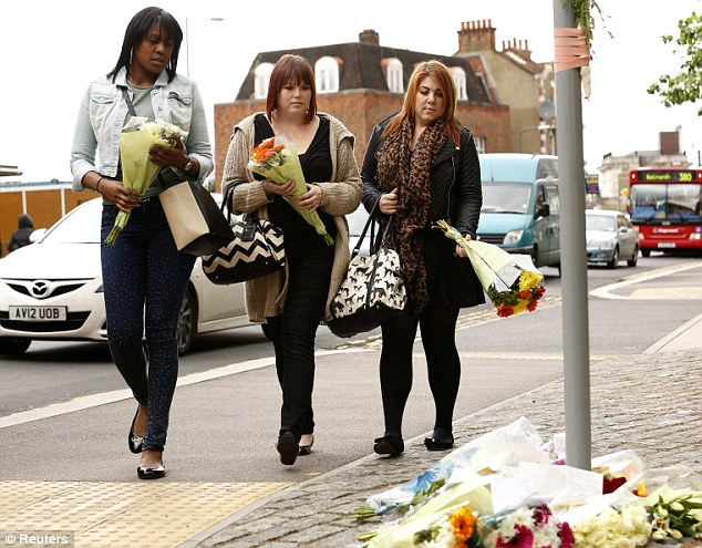 Moved: Three young women prepare to lay flowers where the unnamed soldier was murdered brutally yesterday