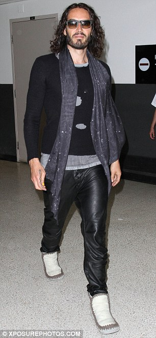 Funny man: Russell arrived at the airport in leather pants, scarf and mocassins
