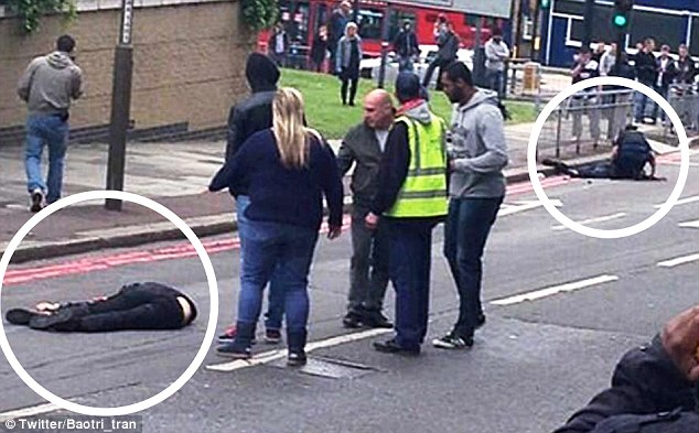The victim lies on the floor (circled left) while the man believed to be Michael Adebolajo is treated by a police officer (circled right)