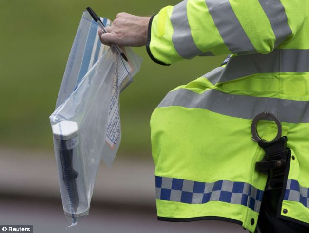 A police officer carries a knife in an evidence bag from the scene of the brutal attack