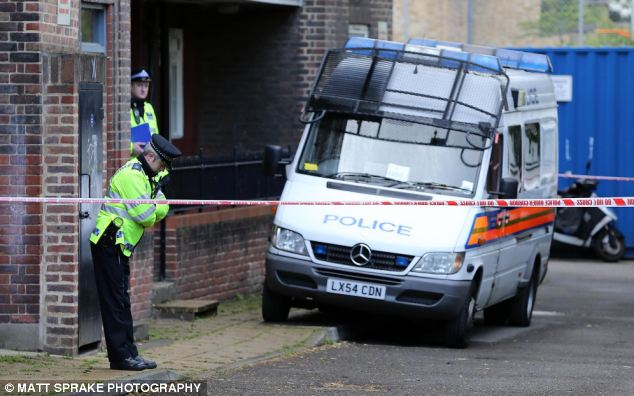 Police stand outside a ground floor flat on Old Woolwich Road today in one of a series of raids across London