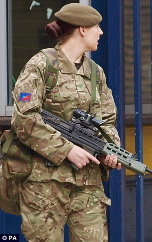 High security: An armed woman stands guard outside the Royal Artillery Barracks in Woolwich as security is stepped up at military bases across the country following yesterday's attack