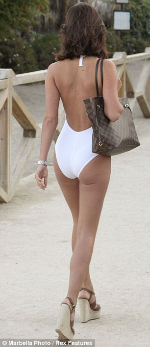 White hot: Lucy teamed the one-piece with a pair of towering heels to make her legs look even longer