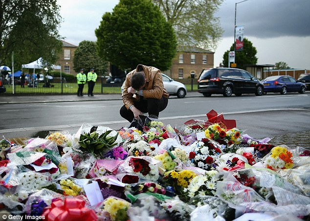 Grief: A wellwisher outside the army barracks, 200 yards from where Drummer Lee Rigby was killed, by the huge - and growing - pile of flowers