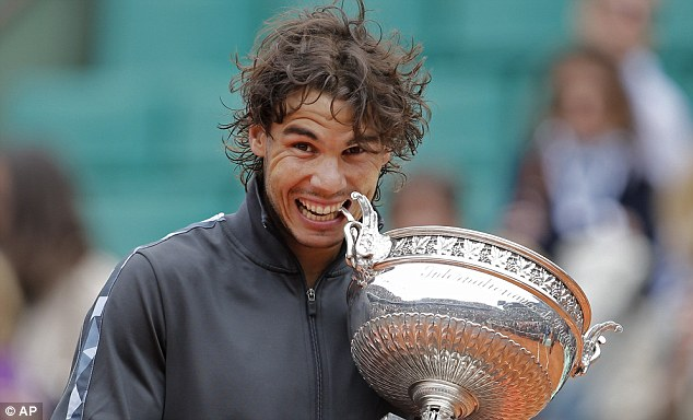 Defending champion: Rafael Nadal bites the French Open trophy after winning the title last year
