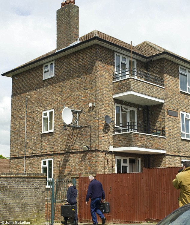 Search: Police and forensic officers enter the top floor flat in Romford, Essex, where Adebolajo's sister Blessing lives. Neighbours said he used to live at the property