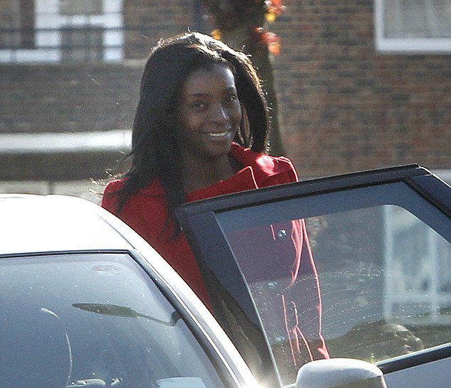 Suspect's sister: Blessing Adebolajo, 32, smiles as she gets into an unmarked police car outside her home in Romford, Essex, yesterday morning