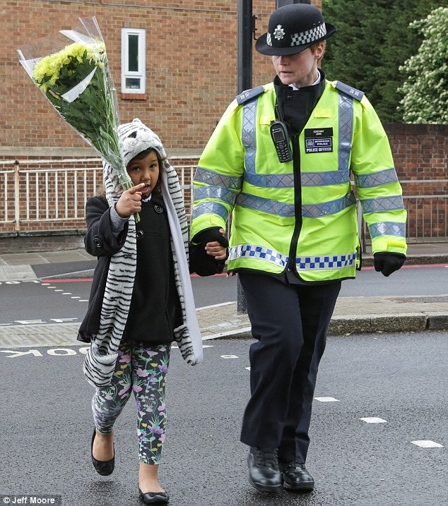 Partnership: A police officer walks a young girl by the hand to leave flowers as the community comes to terms with the brutal murder