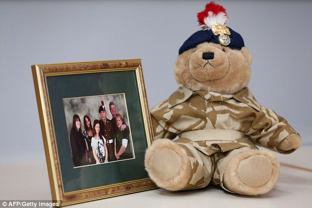 Memories: A teddy bear bought by murdered soldier Drummer Rigby for his son, Jack, sits alongside a family photograph at a press conference at the Regimental HQ of his unit today
