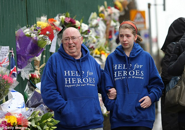 Tribute: Two members of the public wearing Help for Heroes hoodies grip onto eachother and cannot hold back the tears like the one worn by Lee Rigby when he was murdered in cold-blood