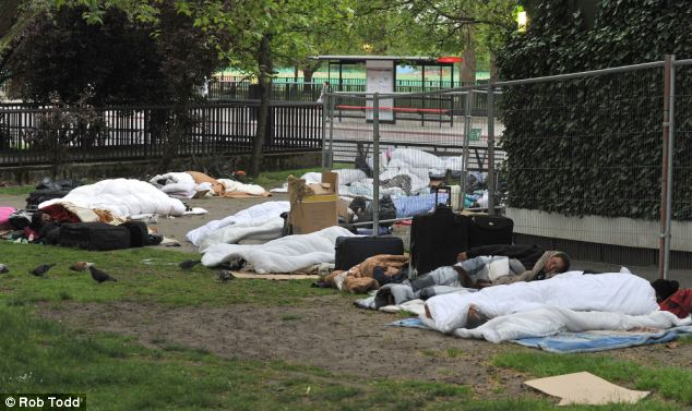 Birds peck their way between the beggars sleeping rough in Park Lane - one of London's most expensive addresses