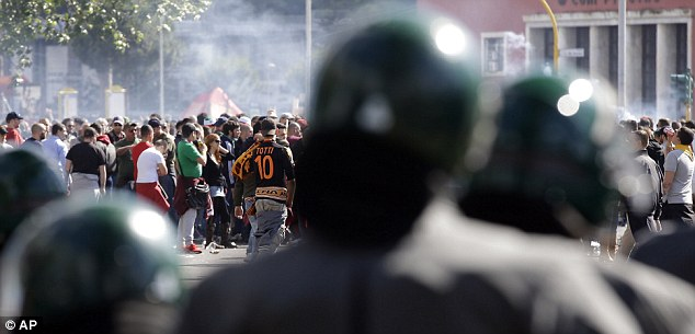 Trouble: Italian police officers patrol outside the Olympic stadium in Rome prior to the match