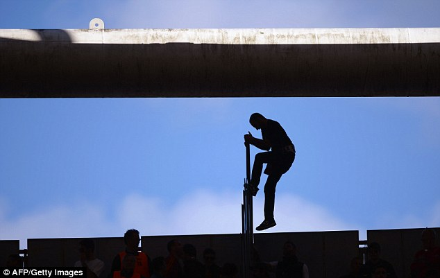 Rebel: A supporter scales a fence on the terrace at the Olympic Stadium