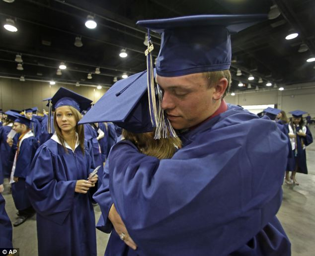 Southmoore High School senior Jake Spradling hugs a classmate as they get ready to attend their commencement ceremony in Oklahoma City on Saturday