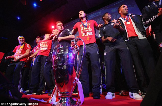 Holy grail: The Bayern players bounce up and down in front of the Champions League trophy