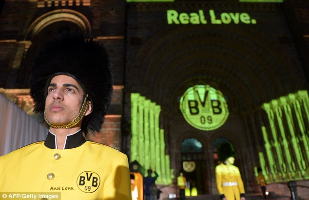 Real love: An actor dressed in Dortmund colours stands guard outside their party in Kensington