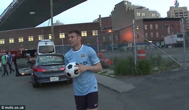 Lads on tour: James Milner gears himself up to try and hit the Brooklyn Bridge from below