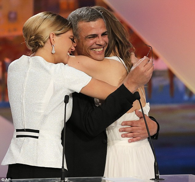 Overjoyed: Director Kechiche is hugged by his two stars as they accept the prestigious award