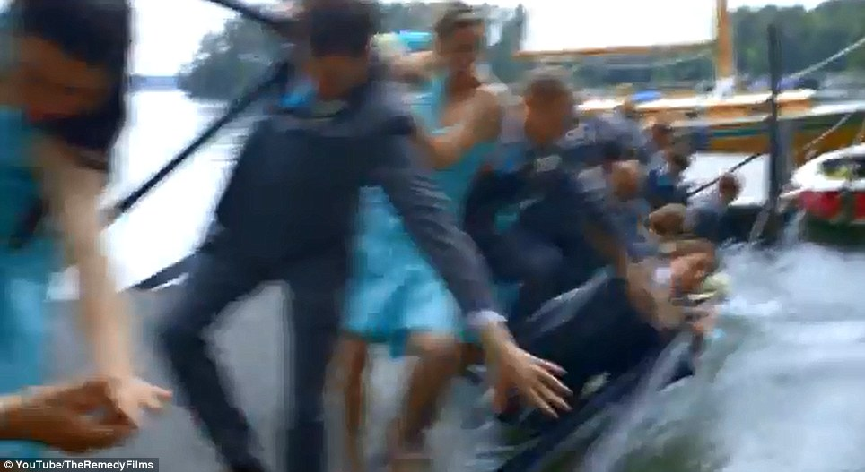 Oops! The wedding party is seen plunging into the water as the dock gives way after a bolt popped out