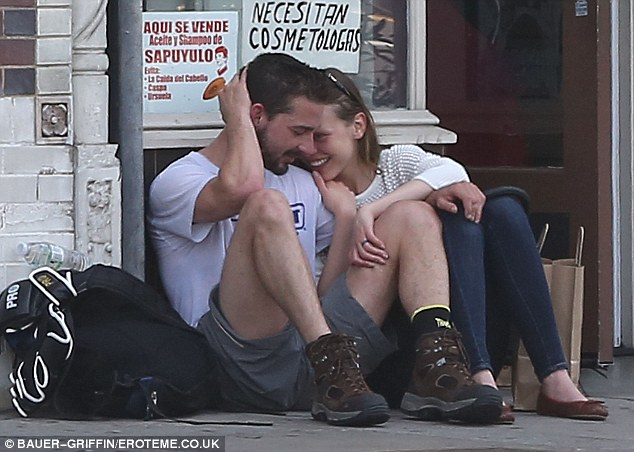 Cuddled up: Shia LaBeouf and girlfriend Mia Goth stopped for a moment on Monday in Los Angeles to sit on the sidewalk and chat