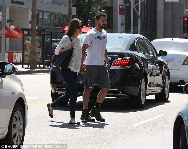 In step: Shia led his 19-year-old girlfriend as they traversed the Hollywood traffic by foot