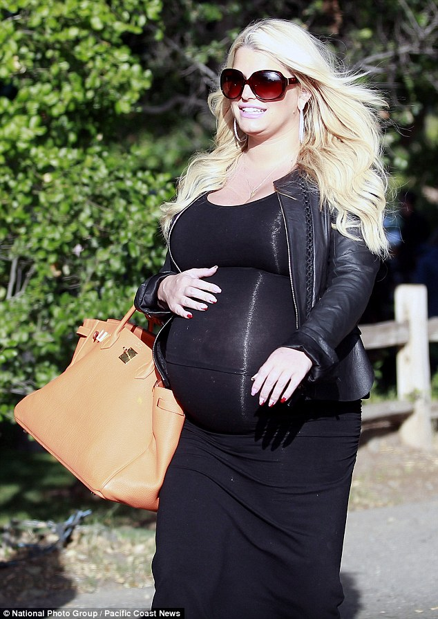 Pregnancy style: As always the star carted a giant designer handbag with her, this time toting a bright orange Hermes Birkin bag