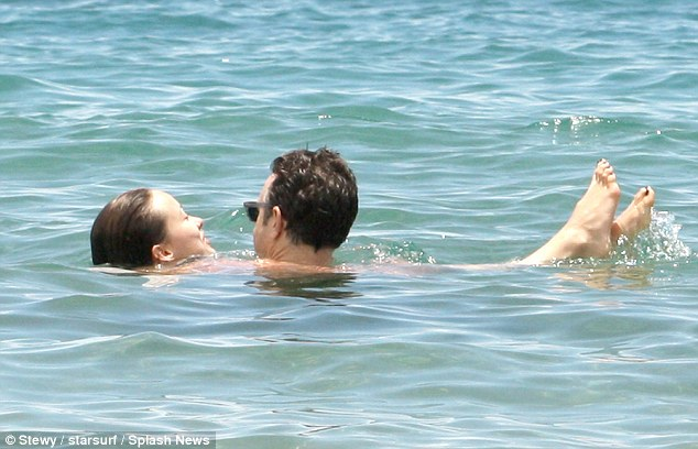 Tan time: Jason helped Olivia float in the water making the most of the sun
