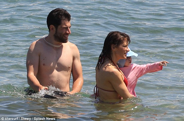 Cooling off: The doting parents cooled off in the shallows with daughter Lilly