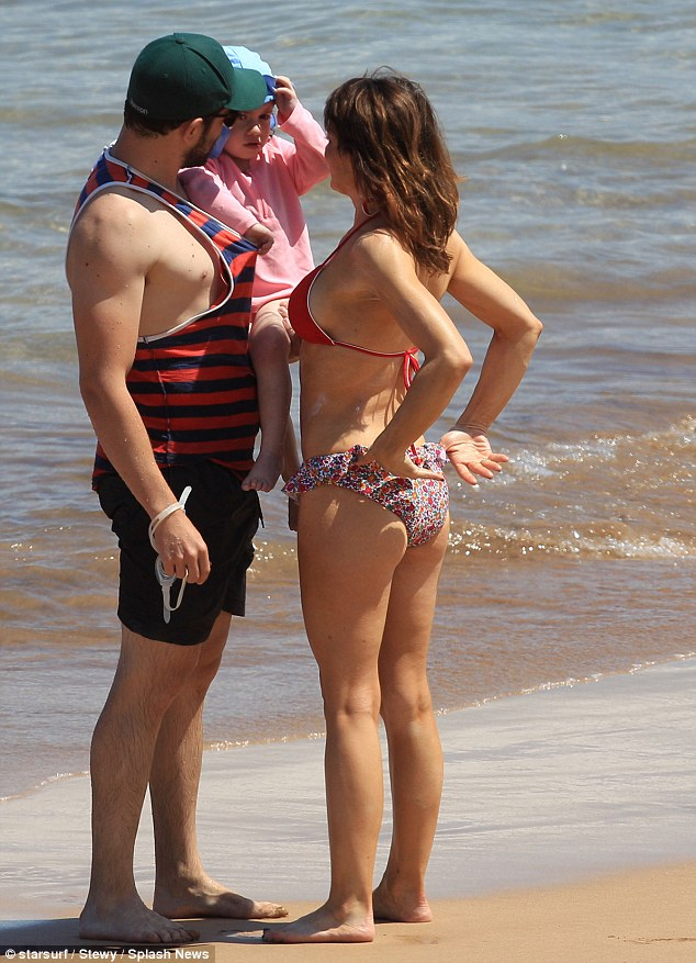 Family affair: Max cradled his three-year-old daughter Lilly while wife Tess joined him on the beach