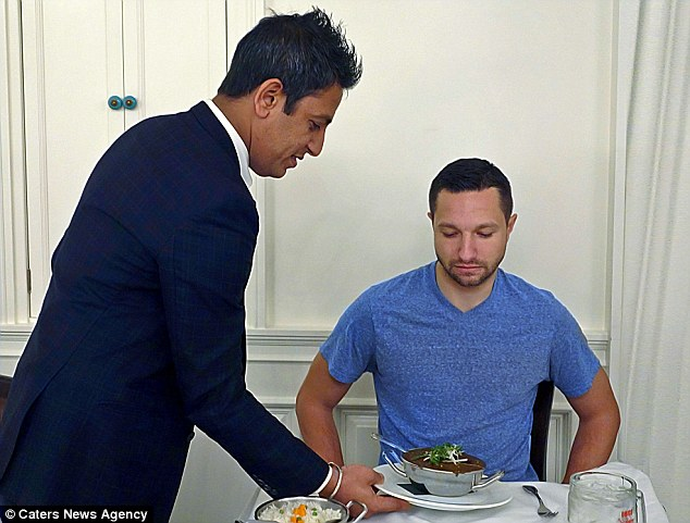 A diner looks nervously on as a waiter brings the potent dish to his table, ready for him to take on the taste challenge