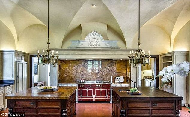 Old touches: Even with a massive remodel that started in 1999 and continued for years, details like the crest on the vent hood above the stove and the arched ceilings pay homage to it's history