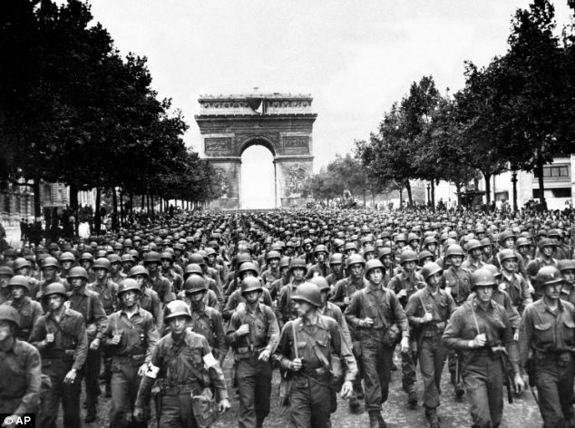 Freedom: Thousands of American soldiers are seen marching on Paris after the city's liberation in August 1944