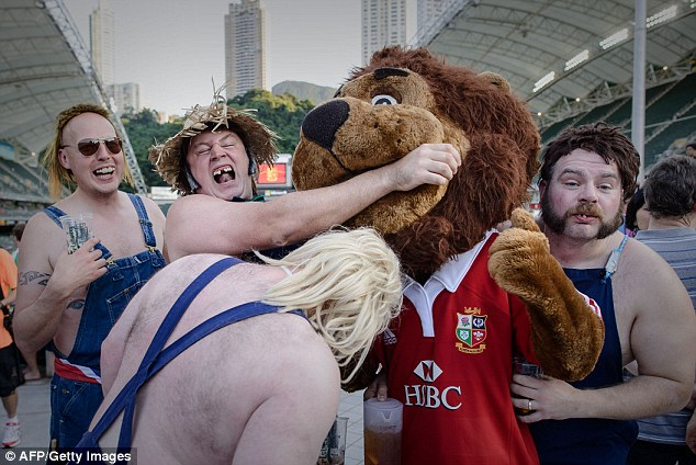 First blood to the Lion: Some very handsome supporters joke around with the mascot