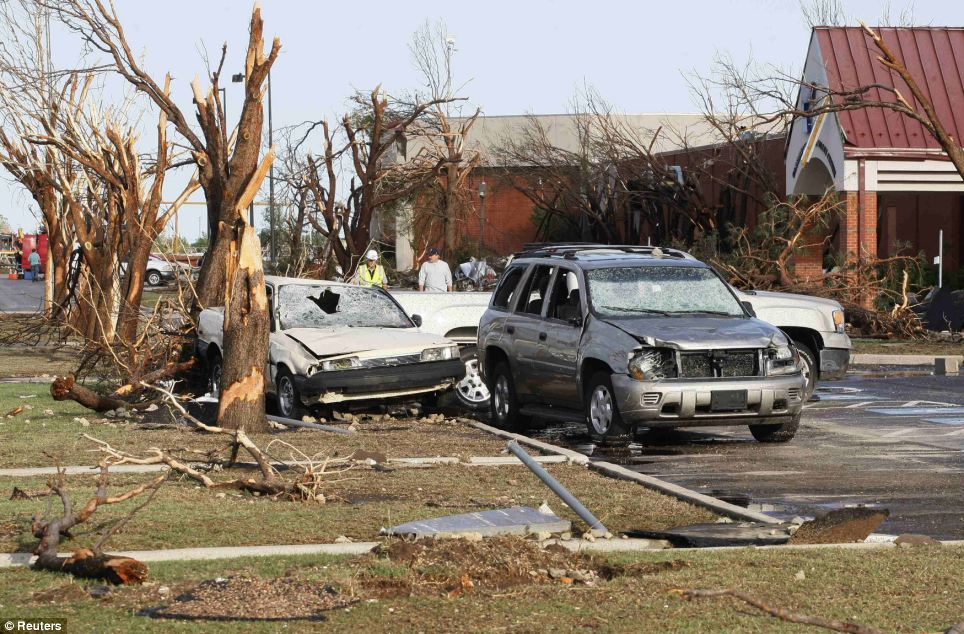 People walk near cars and trees damaged by a tornado at the Canadian Valley Technology Center in El Reno, Oklahoma on Saturday morning