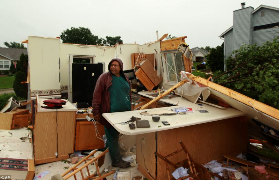 The morning after: Wilburn Shaw looks for personal items in the remains of his kitchen the morning after Friday night's storm that passed through St. Charles, Mo
