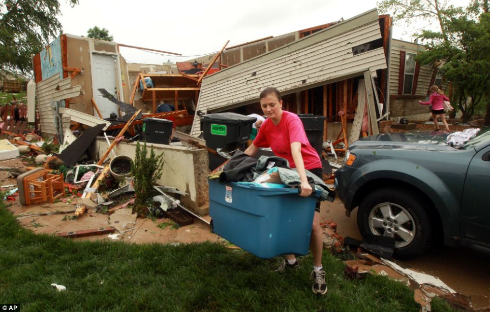 A woman helps salvage clothing from her neighbor's destroyed house on Saturday morning after overnight storms in St. Charles, Mo.